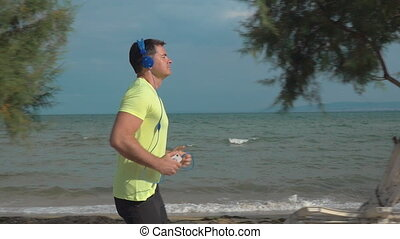 Jogging with music and smartphone at the seaside