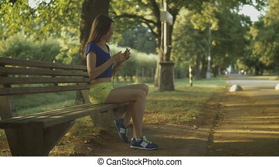 Jogging woman setting music on mp3 player before run -...