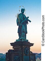 John of Nepomuk Statue on Charles Bridge in Prague in early morning.