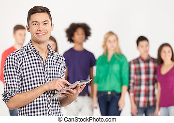 Join a digital age. Cheerful young man holding digital tablet while his friends standing on background