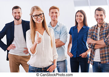 Join a successful team! Beautiful young woman showing her thumb up and smiling while group of happy young people standing on background and smiling