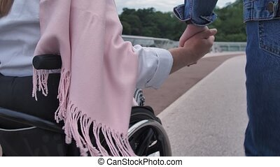 Joined hands of daughter and mother on wheelchair