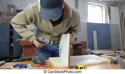 Joiner assembling furniture in workshop