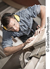 Joiner carefully cutting wooden plank with sawing machine