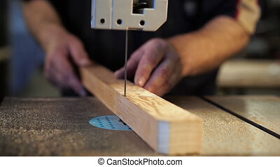 Joiner labourer cuts wooden plank on jigsaw machine. ...