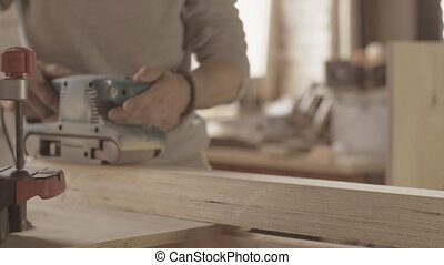 Joiner process of wooden board by belt sander. Move forward and backward