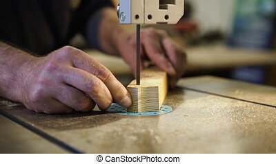 Joiner working in studio. Woodworker cuts wooden plank on ...