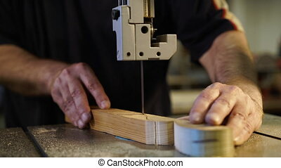 Joiner working in studio. Woodworker cuts wooden plank on ...