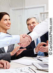 Businessmen shaking hands, their colleagues applauding cheerfully