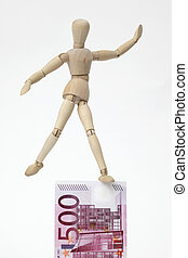 Jointed doll balancing on a 500-Euro-Banknote