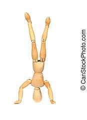 Jointed wooden mannequin doing handstands