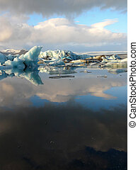 Reflection of floating icebergs inside Jokulsarlon glacier lake in Iceland.