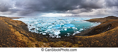 Beautiful 180 degree panoramic view of the floating blue ice in the Jokulsarlon lake in Iceland in winter