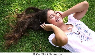 jolie fille, herbe, écoute, musique, mensonge