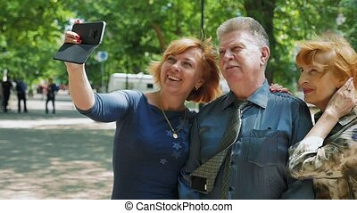 Jolly blond woman is taking a selfie together with her elderly parents in slo-mo