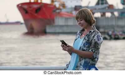 Jolly blond woman surfing on her phone sitting on rails on...