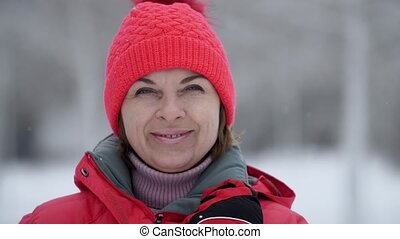Jolly blonde woman standing and smiling outdoors in snowy forest in slow motion