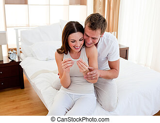 Jolly couple finding out results of a pregnancy test in...