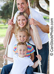 Jolly family swinging in a park
