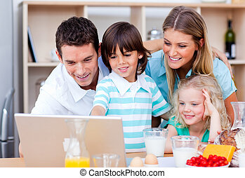 Jolly family using laptop during the breakfast in the...