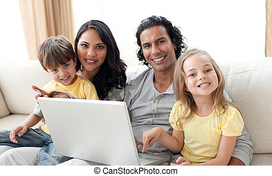 Jolly family using laptop on sofa