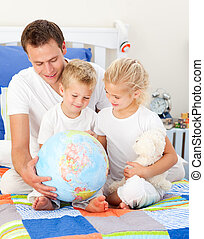 Jolly father and his children holding a terretrial globe