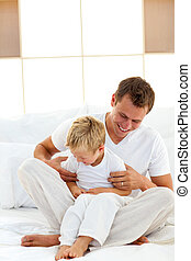 Jolly father playing with his boy on a bed