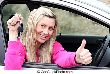 Jolly female driver showing a key after bying a new car