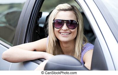 Jolly female driver wearing sunglasses sitting in her car...