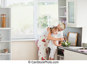 Jolly girl preparing a salad with her mother