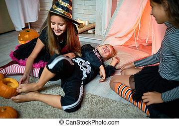 Jolly girl tickling foot of friend - Playful cute little...