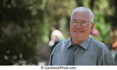 Jolly grey-headed man in glasses stands and smiles in a park...