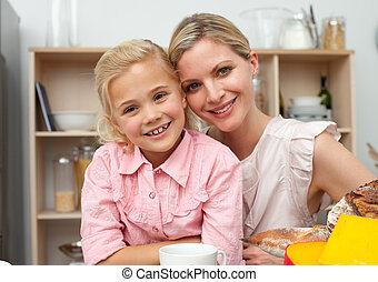 Jolly little girl eating fruit with her mother