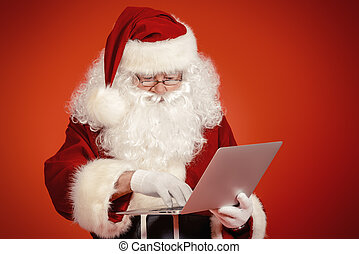 jolly man - Modern Santa Claus using laptop computer over...