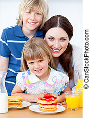 Jolly mother and her children eating waffles with strawberries in the kitchen