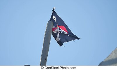 Jolly Roger Pirate flag develops against the blue sky -...