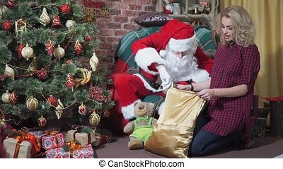 Jolly Santa looks in the bag with gifts surprised girl