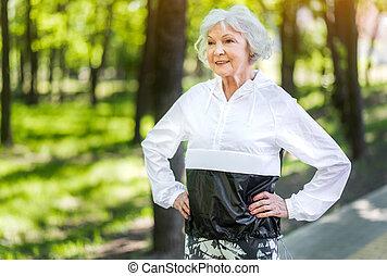 Jolly senior lady training among green trees