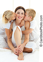 Jolly siblings kissing their mother sitting on a bed