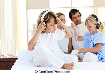 Jolly siblings listening music with headphones