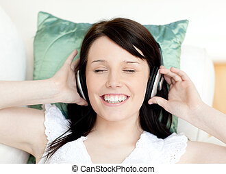 Jolly teen girl listening music lying on a sofa