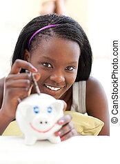 Jolly teen girl putting money in a piggy-bank