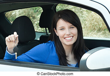 Jolly teen girl sitting in her car holding keys after bying...