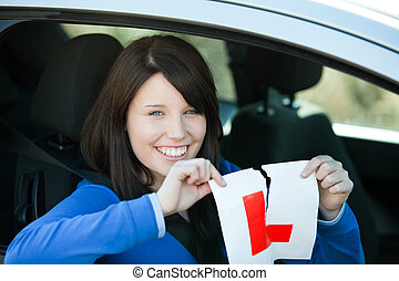 Jolly teen girl sitting in her car tearing a L-sign after...