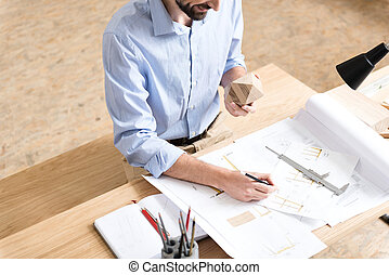 Jolly woodworker with beard creating design of new manufacture indoor