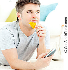 Jolly young man holding a remote eating crisps lying on the floor in the living-room