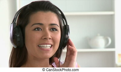 Jolly young woman listen to music sitting on the couch...