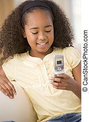 jong meisje, in, woonkamer, gebruik, cellulaire telefoon, en, het glimlachen