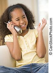 jong meisje, in, woonkamer, gebruik, telefoon, en, het glimlachen