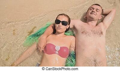 jong paar, het liggen, in, water, op het strand, 2